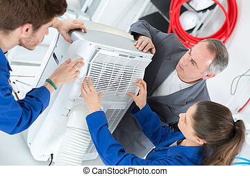 Young people woking on air conditioning unit