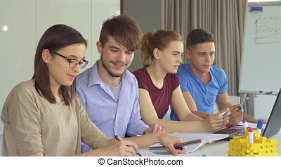 Young people work in pairs at the office