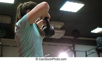Young people working out their arms using in a cross-training gym
