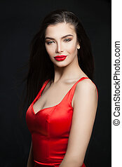 Young perfect brunette woman with red lips makeup and dark hair on black background