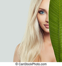 Young perfect female face. Beautiful blonde woman with healthy skin and green leaf. Natural beauty