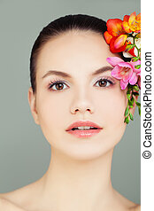 Young Perfect Female Face. Spa Woman with Healthy Skin and Flowers