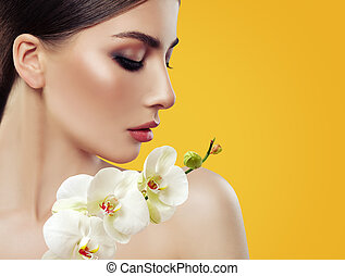Young Perfect Woman Face with Makeup and Orchid Flowers on Bright Yellow Background, Beauty Portrait
