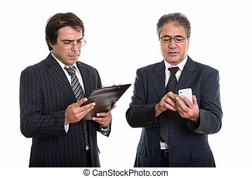 Young Persian businessman reading on clipboard and senior Persia