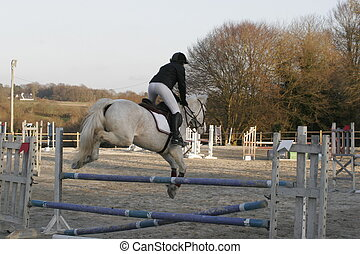 young person on horse, jumping over a fence