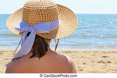 Young person with straw hat by the beautiful sea