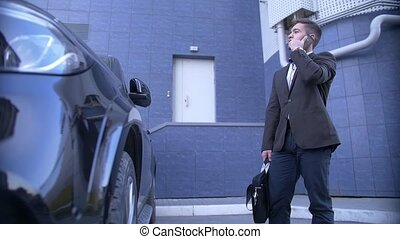 Young perspective businessman talk on mobile, stands beside with fashionable car