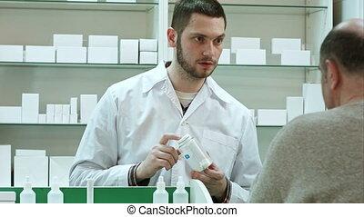 Young pharmacist advicing pills senior man customer at drugstore