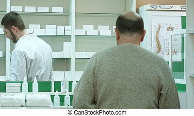 Young pharmacist and senior man customer with drug and prescription at drugstore