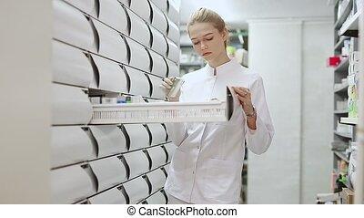Positive woman pharmacist browsing rows of drugs in pharmacy