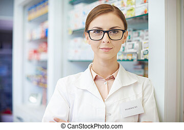 Young pharmacist standing in drug store