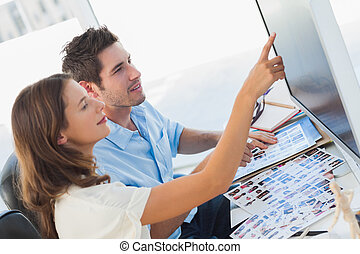 Young photo editors pointing at a computer screen