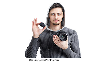 young  photographer holds the battery for DSLR digital camera is