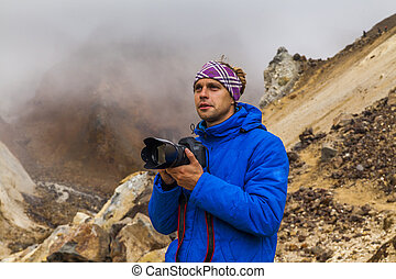 Young photographer on the background of volcanic rocks. Kamchatka.