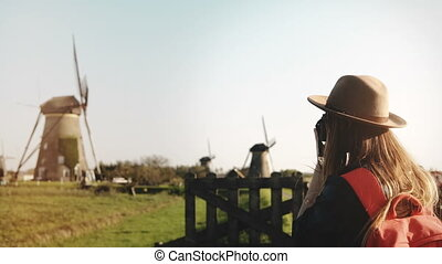 Young photographer takes a photo of old windmill. Blogger...