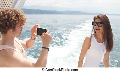 Young photographer taking picture of his girlfriend on sea...
