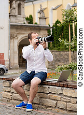 Young photographer with laptopon stone bench andtaking photo on camera