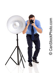 young photographer working in studio - young male...