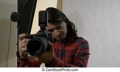 Young photography student with dark hair on his first day at work in a professional studio checking the camera before photo session