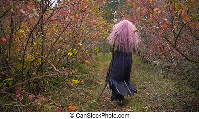 Young pink hair witch in hat pursues me in the mystical autumn forest. Halloween is coming.