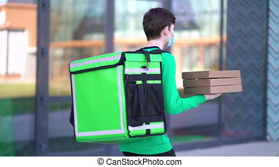 Young pizza courier is delivering an order. Delivery man ...