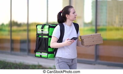 Young pizza courier is delivering an order. Delivery woman ...