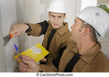 young plasterer applying the filler