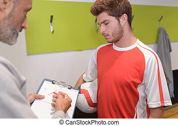 young player talking game strategy with coach in changing room
