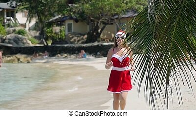 Young playful woman in santa hat look out from palm tree of branch on tropical beach in slow motion. 1920x1080