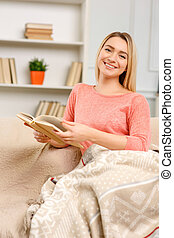 Young pleasant woman reading a book.