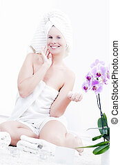 Young pleasure woman is body care in the spa.