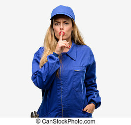 Young plumber woman with index finger on lips, ask to be quiet. Silence and secret concept