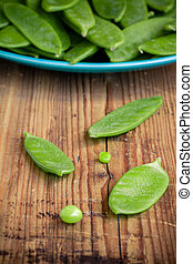 pods of green peas on a wooden background - young pods of ...