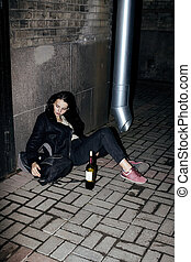 young poor ttenage girl sitting at dirty wall on floor with bottle of vine, poor refugee alcoholic, hopeless homeless woman in depression, real junky concept