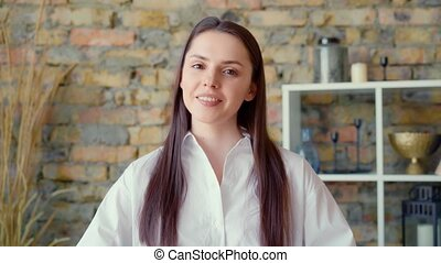 Young positive businesswoman looking at camera and talking