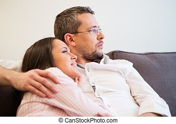 Young positive couple on a sofa in home interior