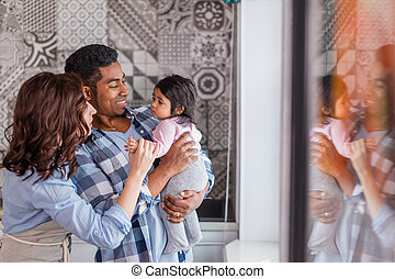 young positive couple playing with their little child at home