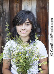 Young positive girl with a bouquet of wild flowers in the village