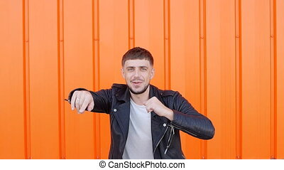 Young positive male brunette in a black jacket is dancing on an orange background, close-up, caucasian, slow motion