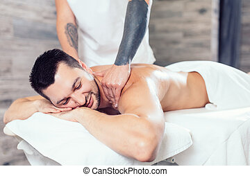 young positive man enjoying getting massage in the spa center