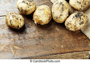 young potato is scattered on a wooden background