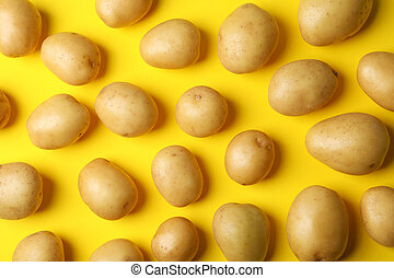 Young potato on yellow background, top view