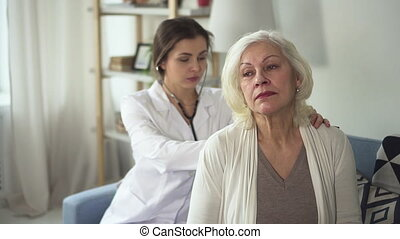 Young practitioner is listening to adult patient using stethoscope on woman back by slow motions.