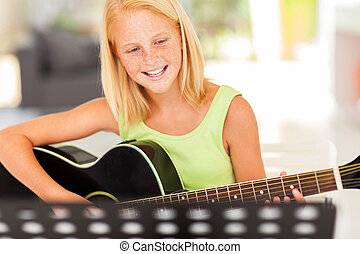 young pre teen musician playing guitar - cheerful young pre...