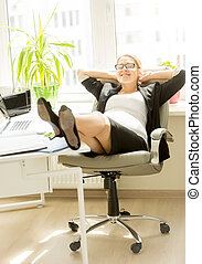 Young pregnant businesswoman relaxing at office chair