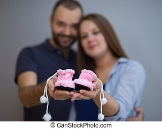 pregnant couple holding newborn baby shoes