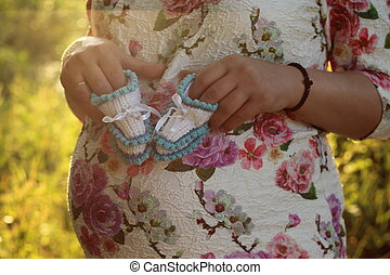 Young pregnant girl. Hands of a pregnant girl holding a close-up of baby booties in the park