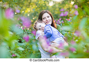 Young pregnant mother holding her tired baby daughter in a park