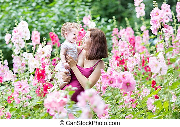 Young pregnant mother playing with her baby daughter in a beauti