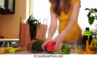 Young pregnant wife unload natural vegetables from shopping bag on kitchen table